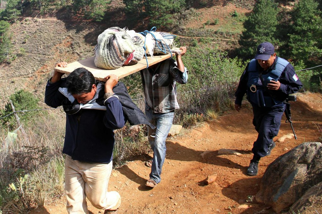 Local residents carry the corpse of one of the eleven members of a family shot dead at El Mirador village in Coxcaltlan, Puebla state, Mexico, on June 10, 2016. Gunmen marched into a remote mountain village in Mexico on Friday and killed 11 members of the same family, including two children, authorities said. / AFP PHOTO / SAUL MUNOZ